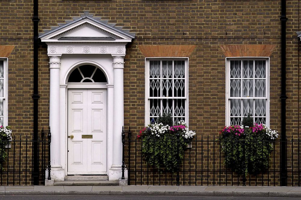 All white door and white framed windows on brick facade