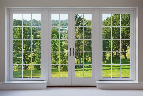 White french doors and windows showing a view of trees
