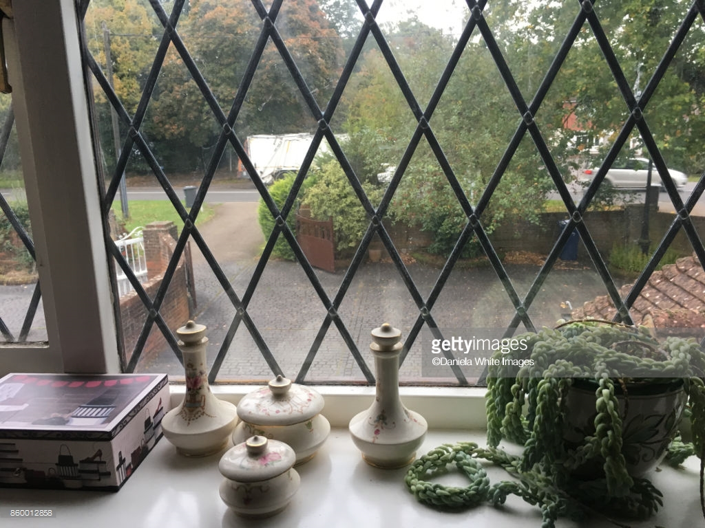 Interior view of leaded window design with trinkets on the windowsill