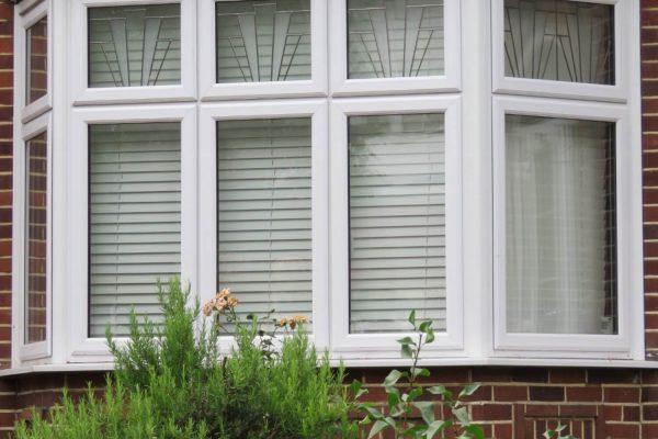 White framed windows on a brick facade