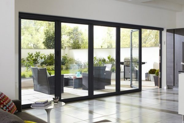 Mostly closed bi-fold doors showing view of patio with barbeque and dining area