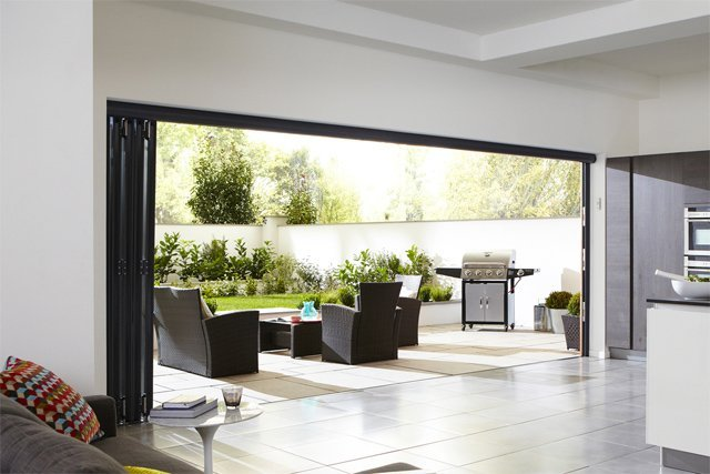 Open bi-fold doors showing view of patio with barbeque and dining area