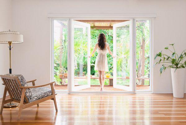 Woman walking through uPVC doors to the garden